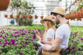 Young gardeners with clipboards filling orders of flowers in greenhouse