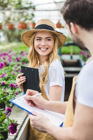 Photo pour Jeunes jardiniers mâles et femelles, tenant des planchettes à pince de fleurs en serre - image libre de droit