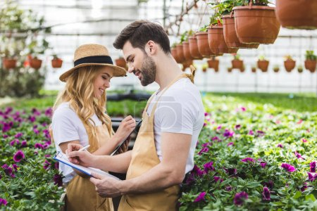 Photo for Couple of gardeners holding clipboards by flowers in greenhouse - Royalty Free Image
