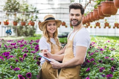 Photo for Young gardeners holding clipboards by flowers in greenhouse - Royalty Free Image