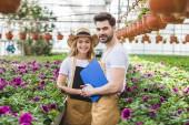 Couple de jardiniers tenant des planchettes à pince de fleurs en serre