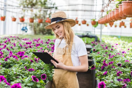 Young female owner of glasshouse with clipboard filling order of flowers