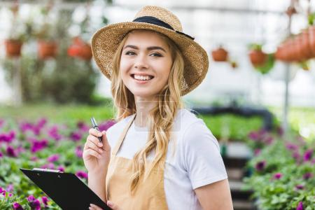 Blonde woman holding clipboard by flowers in greenhouse