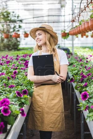 Attractive female gardener holding clipboard by flowers in greenhouse