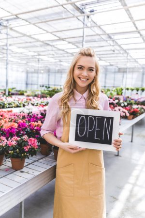 Smiling female owner of glasshouse holding Open board by flowers in greenhouse