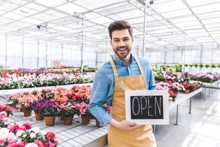 Male owner of greenhouse with Open board by flowers