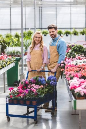 Male and female gardeners standing by cart with flowers in greenhouse