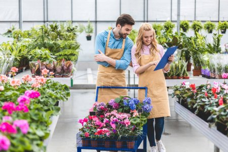 Photo pour Sourire des jardiniers avec presse-papiers remplissant de commande de fleurs en serre - image libre de droit