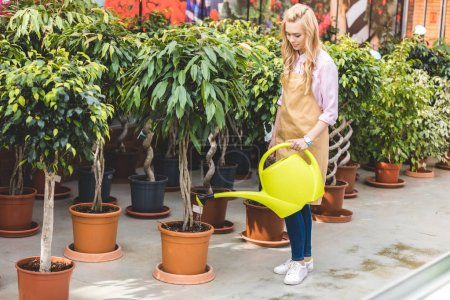 Blonde woman watering green plants in glasshouse