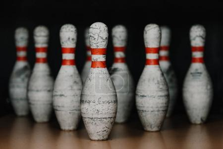 close-up shot of grungy bowling pins in gate on black