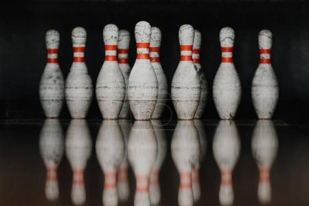 grungy bowling pins in gate with reflection in polished floor
