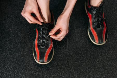 cropped shot of woman tying up rental bowling shoes