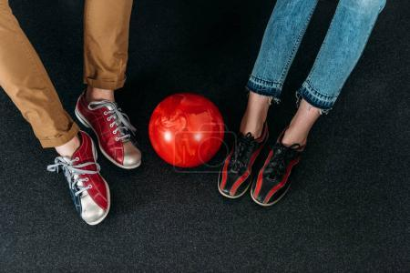 cropped shot of couple in rental bowling shoes with ball