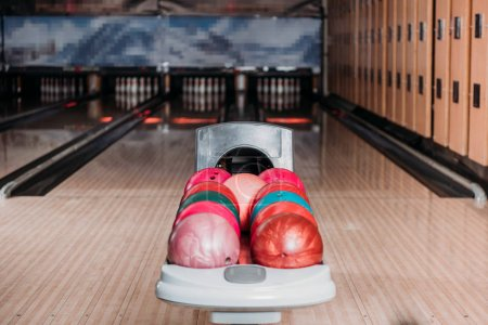 stand with colorful bowling balls in club against alleys