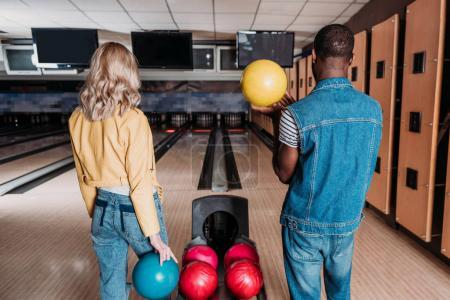 multiethnic couple with bowling balls standing in front of alleys at club