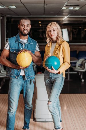 happy young couple with bowling balls looking at camera at club