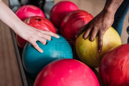 cropped shot of man and woman taking bowling balls from stand