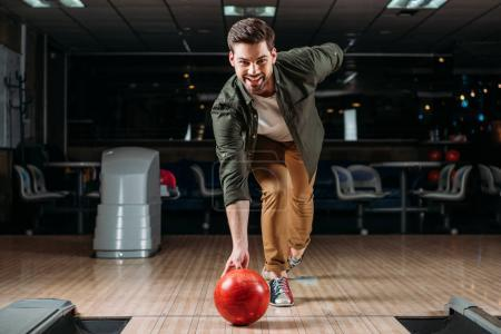 happy young man throwing bowling ball and looking at camera