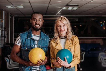 young couple with bowling balls looking at camera at club