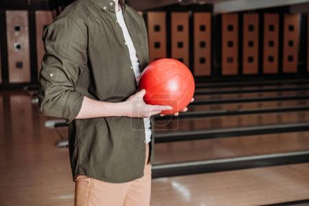 cropped shot of man holding bowling ball at club
