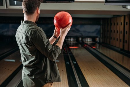 rear view of man with bowling ball looking at alleys