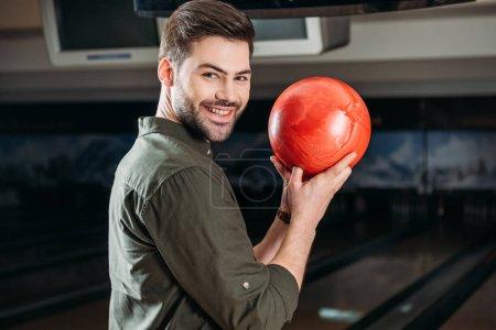 Photo pour Souriant jeune homme tenant boule de bowling et regardant la caméra - image libre de droit