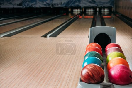 stand with colorful bowling balls in club in front of alleys