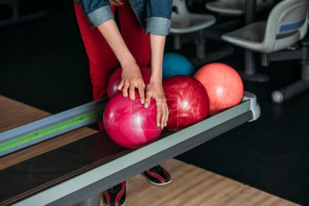 cropped shot of woman taking bowling ball from stand
