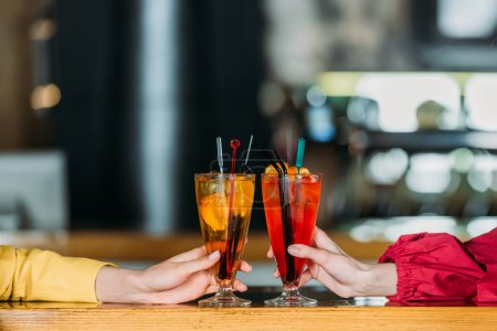 cropped shot of women holding glasses of cocktails at bar counter