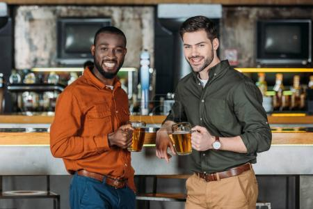 happy young men with mugs of beer at bar counter looking at camera