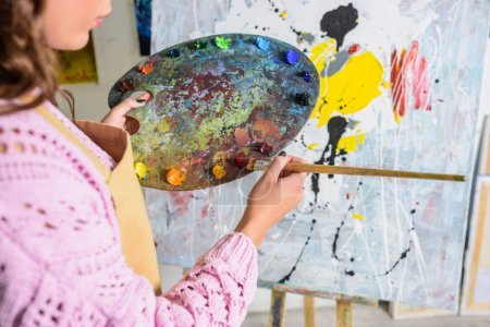 Photo for Cropped image of female artist taking paint from palette in workshop - Royalty Free Image