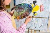 Cropped image d'artiste féminine en peinture de la palette atelier