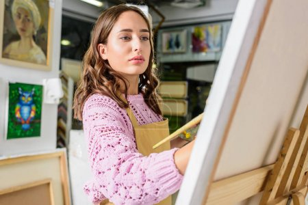 attractive female artist painting in workshop