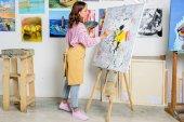 """Постер, картина, фотообои """"вид сбоку красивых женщин художника, живопись на холсте в мастерской"""""""