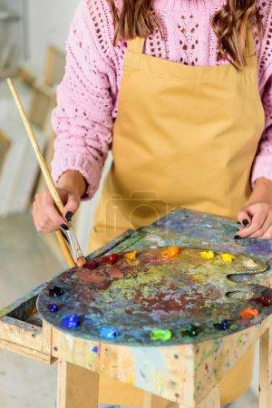 Photo pour Cropped image du peintre application des peintures sur la palette dans l'atelier - image libre de droit
