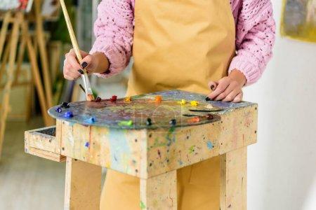 Photo pour Cropped image d'artiste féminine, application de peintures sur la palette dans l'atelier - image libre de droit