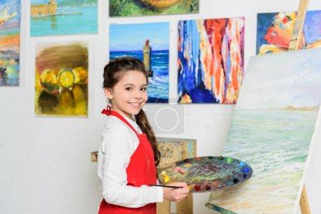 niño preadolescente sosteniendo paleta cerca de lienzo en taller de la escuela de arte