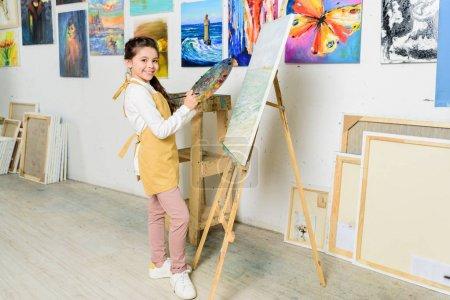 Photo pour Gamin souriant debout près de toile dans l'atelier de l'école d'art et de regarder la caméra - image libre de droit