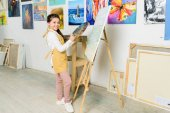 smiling kid standing near canvas in workshop of art school and looking at camera