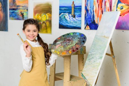 smiling kid holding painting brush and canvas in workshop of art school