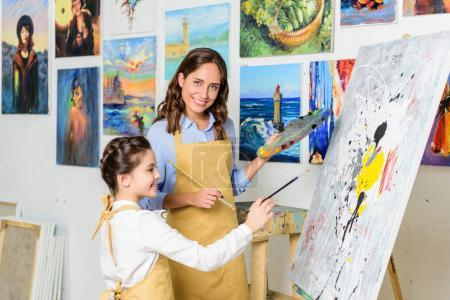 smiling teacher and pupil painting in workshop of art school
