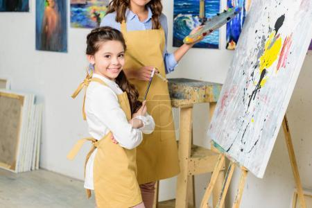 cropped image of smiling pupil standing with crossed arms in workshop of art school