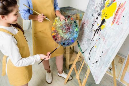 Foto de Recortar imagen de profesor y alumno elegir en la paleta de la pintura en taller de escuela de arte - Imagen libre de derechos