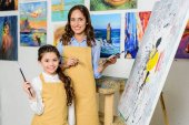 smiling teacher and pupil standing near canvas on easel in workshop of art school