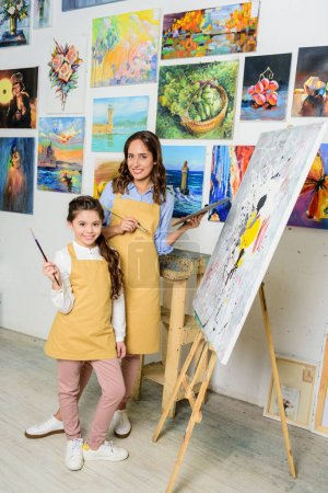 Photo for Teacher and pupil standing near canvas on easel in workshop of art school - Royalty Free Image
