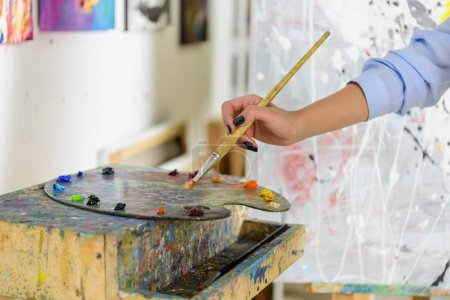 Photo for Cropped image of artist taking paint from palette in workshop - Royalty Free Image