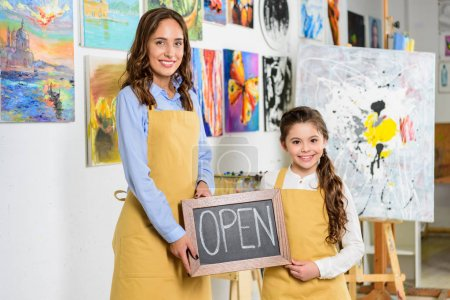 teacher and pupil holding signboard with word open in workshop of art school