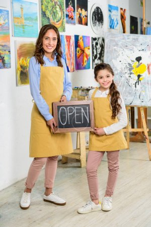 smiling teacher and pupil holding signboard with word open in workshop of art school