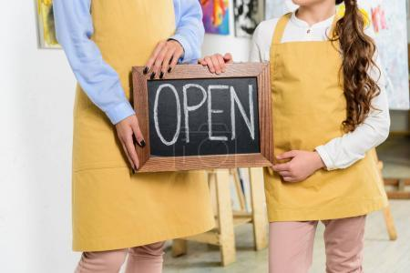 Photo for Cropped image of teacher and pupil holding signboard with word open in workshop of art school - Royalty Free Image
