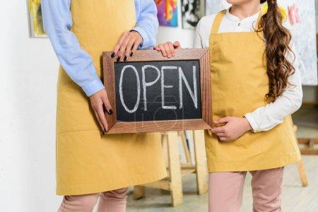 Photo pour Image recadrée de l'enseignant et élève tenant enseigne avec word ouvert dans l'atelier de l'école d'art - image libre de droit